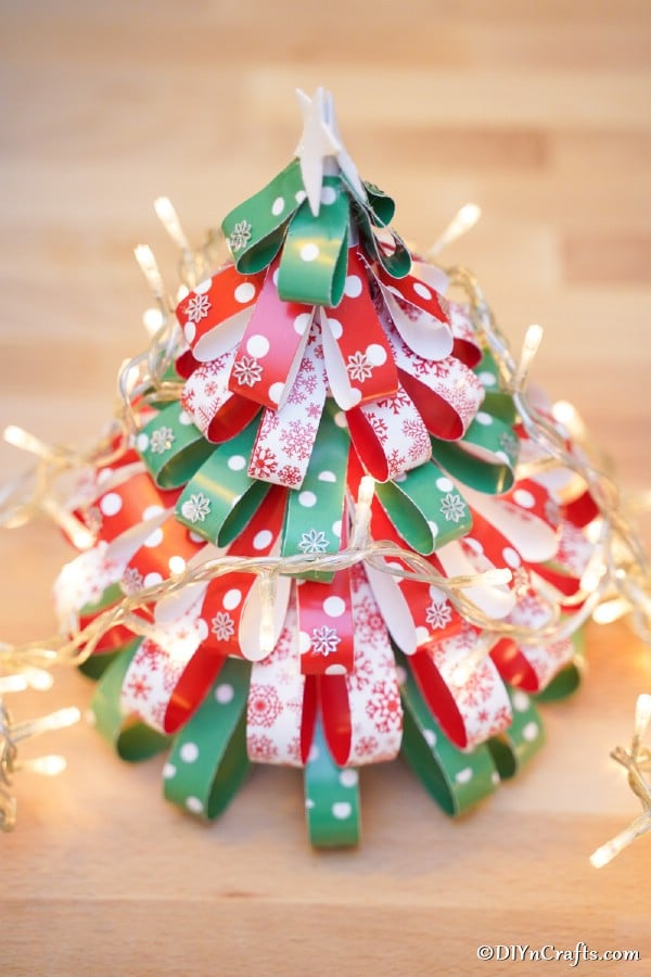 A paper strip Christmas tree on a table with christmas lights around it