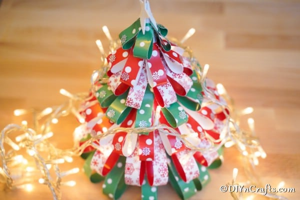 Mini paper strip Christmas tree on a table with twinkle lights