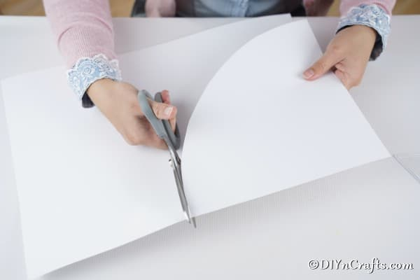 Cutting a cone shape out of white paper for a mini Christmas tree