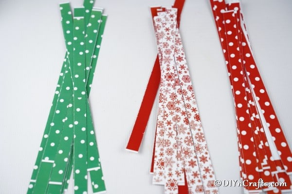 Several paper strips on a white table for making a mini paper strip christmas tree craft