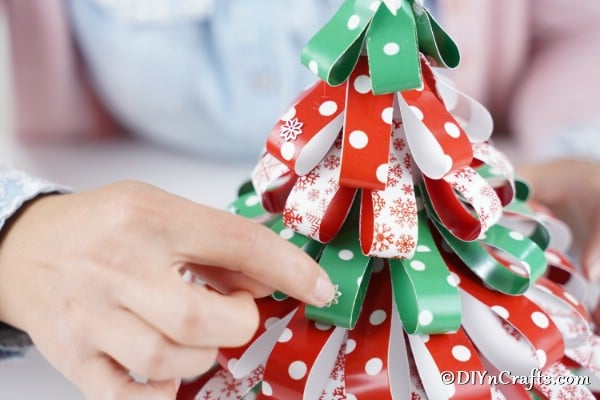 Adding embellishments to the christmas tree made of craft paper