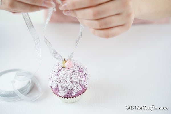 Adding a ribbon to the top of an ornament to make it look like a muffin or cupcake