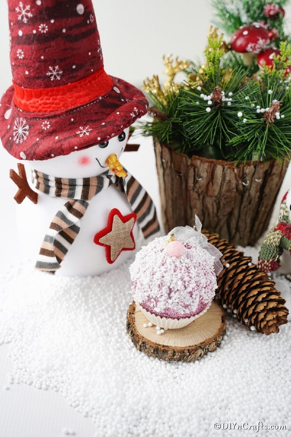 Muffin cupcake ornament on a counter in front of holiday decorations