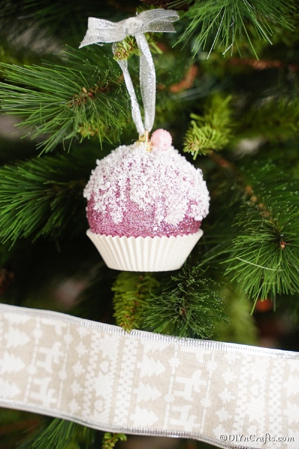 A cupcake ornament hanging on a Christmas tree