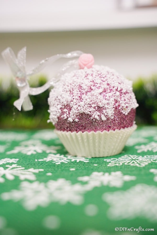 A muffin ornament on a green and white snowflake surface
