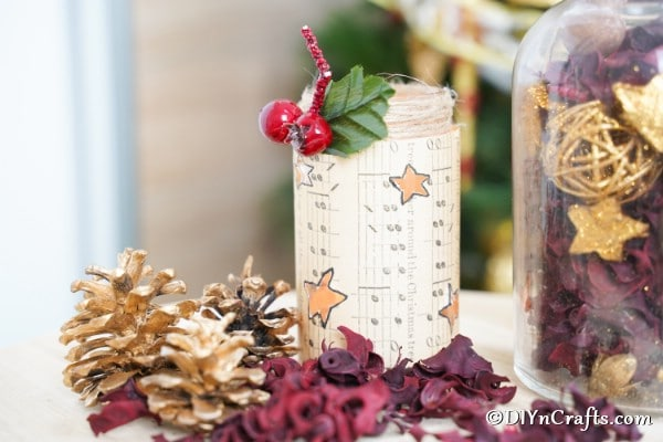 A music sheet lantern sitting in front of holiday decor items with a small mistletoe berry on top