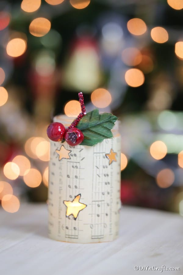 A music sheet lantern for Christmas decoration on a table in front of the Christmas tree