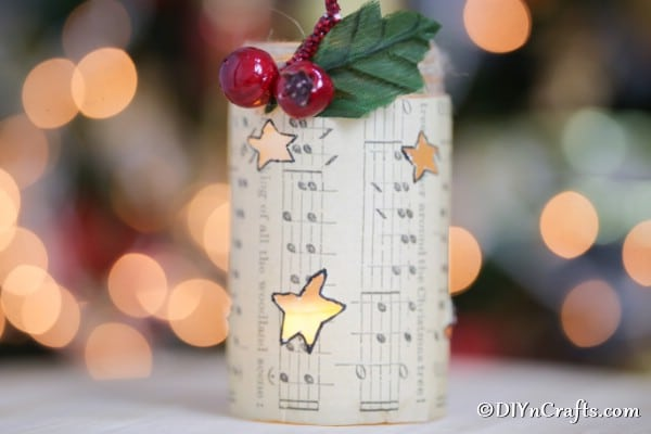 A sheet music lantern on display on a counter in front of a Christmas tree