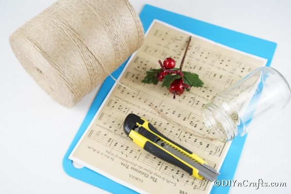 Supplies for making a music sheet lantern on a white table