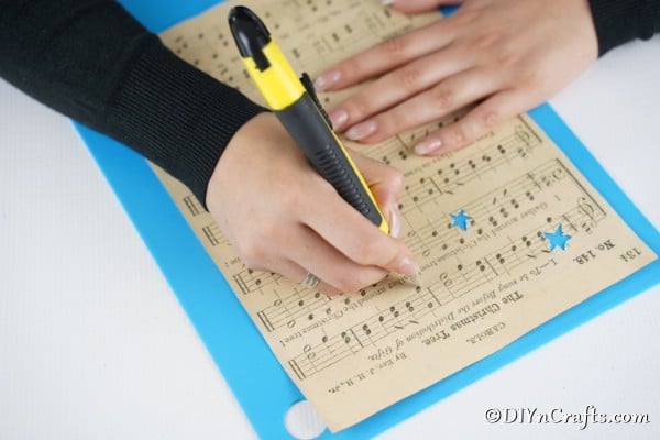 Cutting out star shapes from the sheet music