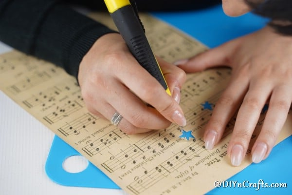 Up close picture of cutting out stars from sheet music paper