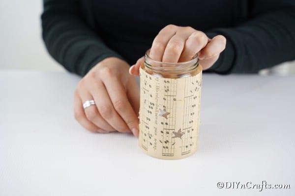 Sealing the music sheet onto the glass jar lantern