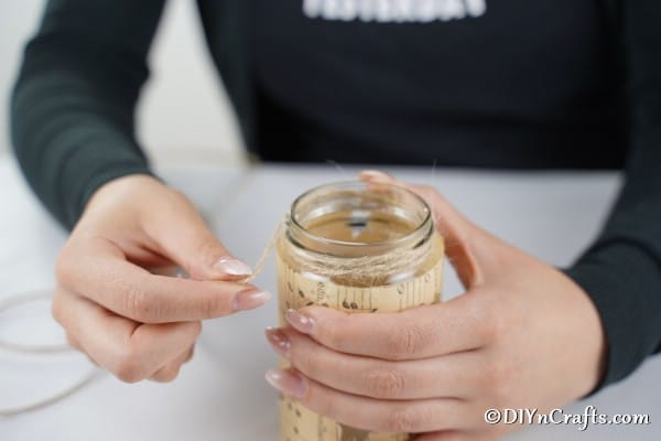Adding twine to the top of the jar for a Christmas lantern decoration