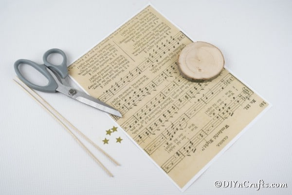 Supplies to make paper Christmas trees from sheet music laying on a white table