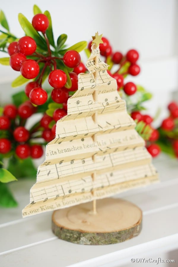 A paper music sheet tree decoration on a mantle with holly berries in the background