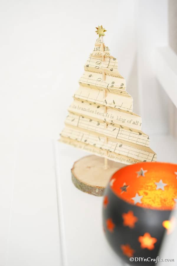 A sheet music paper Christmas tree displayed on the mantle next to a small candle