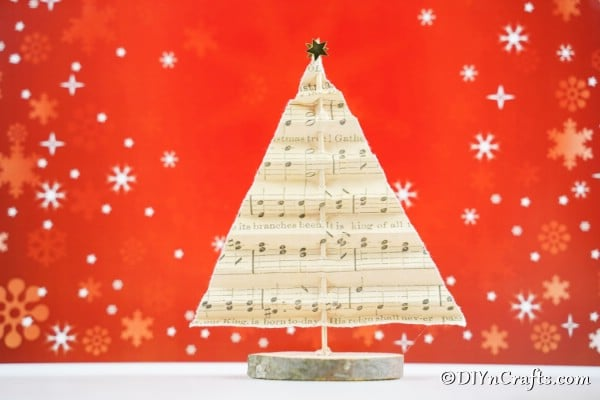 A sheet music paper Christmas tree displayed on a table with a red holiday background