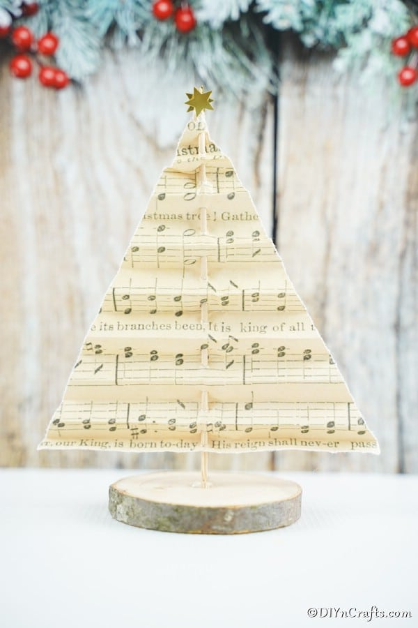 A music sheet paper Christmas tree displayed on a white counter with holiday decor in the background