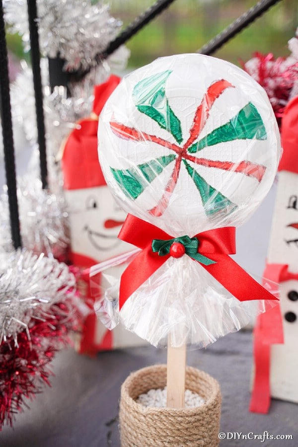Peppermint giant lollipop sitting on a decorated front porch