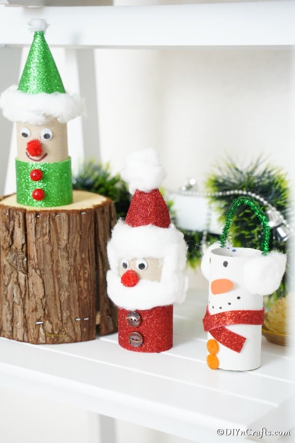 Three toilet paper crafts for Christmas displayed on a mantle