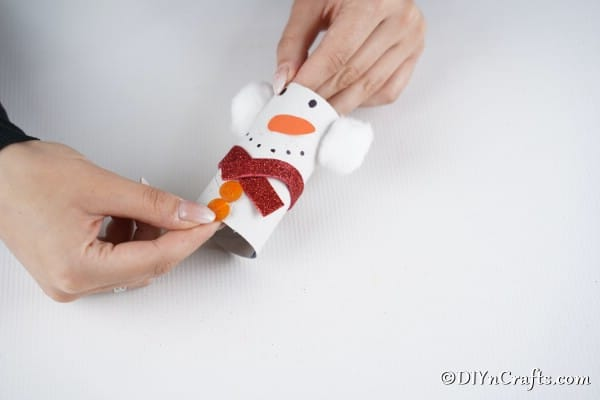 Gluing on a strip of red foam board to create a scarf on the snowman