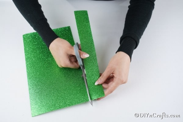 Cutting green strips of paper to create an elf suit