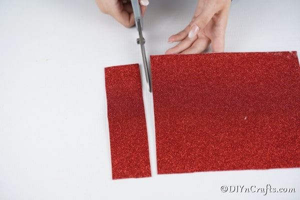 Cutting red foam paper for the santa suit on a paper roll