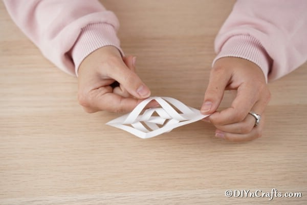 Twisting and folding paper to create a star ornament