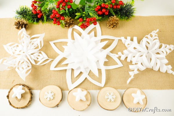 3 snowflake and star designs on burlap with holiday greenery