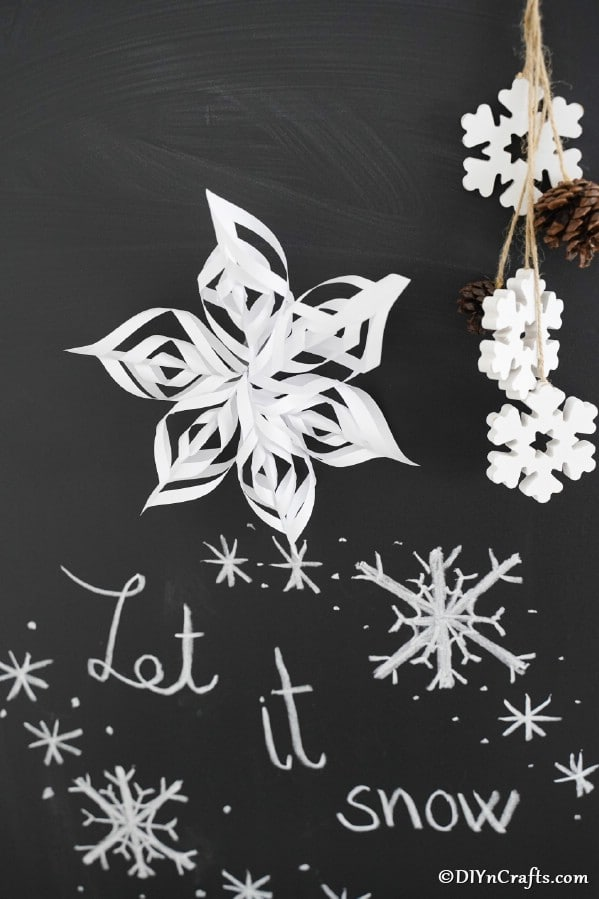 3d snowflake paper ornaments in front of chalkboard sign