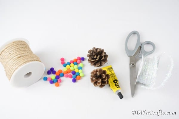 Supplies needed to make a pinecone ornaments with pom poms