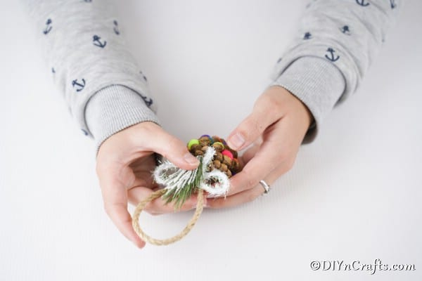 Adding a bow and embellishment to the top of pinecone ornaments