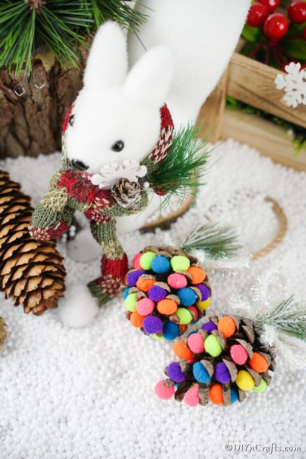 "Colorful pinecone ornaments laying on a counter with white ""snow"""
