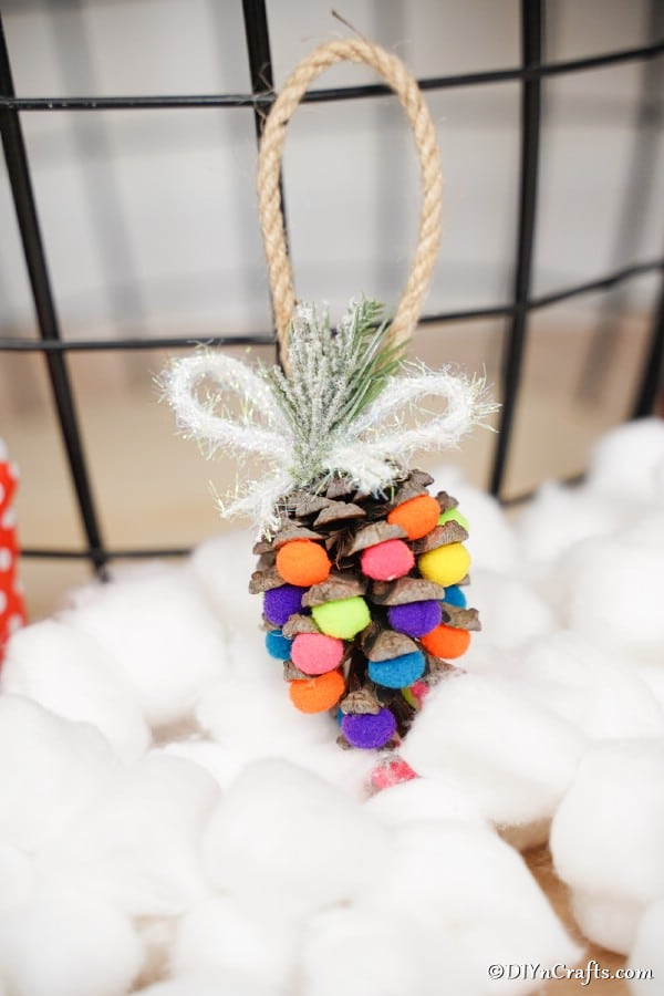 A pinecone ornament with colorful pom poms hanging above a bed of cotton balls
