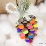 Up close picture of a colorful pinecone ornament against white cotton balls