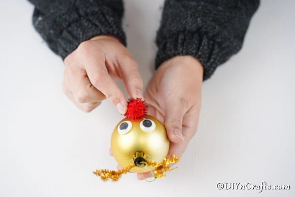 Adding the red pom pom nose to a gold rudolf reindeer ornament