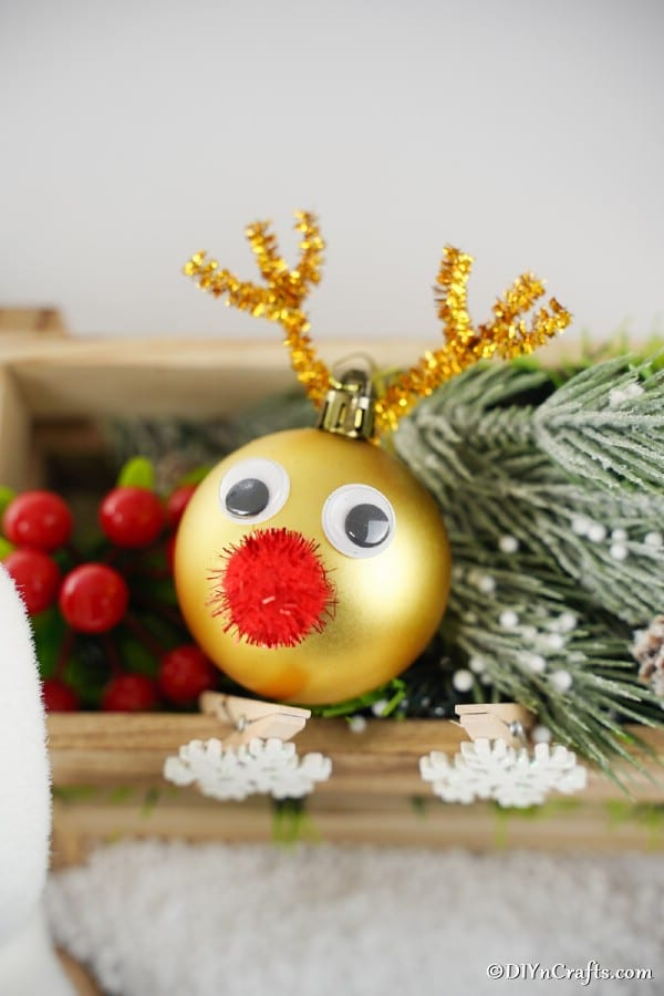 Reindeer Christmas ball ornament on a shelf with holiday greenery