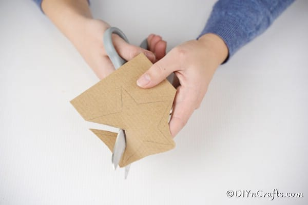 Cutting out a brown star from cardboard for the Christmas star