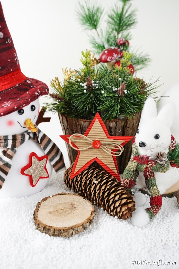 A rustic cardboard Christmas star leaning against a wooden stump