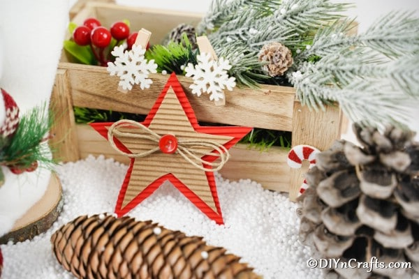A cardboard Christmas star decoration next to a wooden box filled with holiday decorations