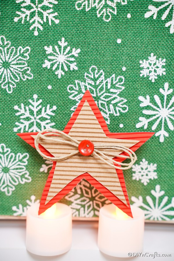 A cardboard Christmas star in front of green background with white snowflakes