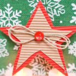 A cardboard star decoration on a green snowflake surface