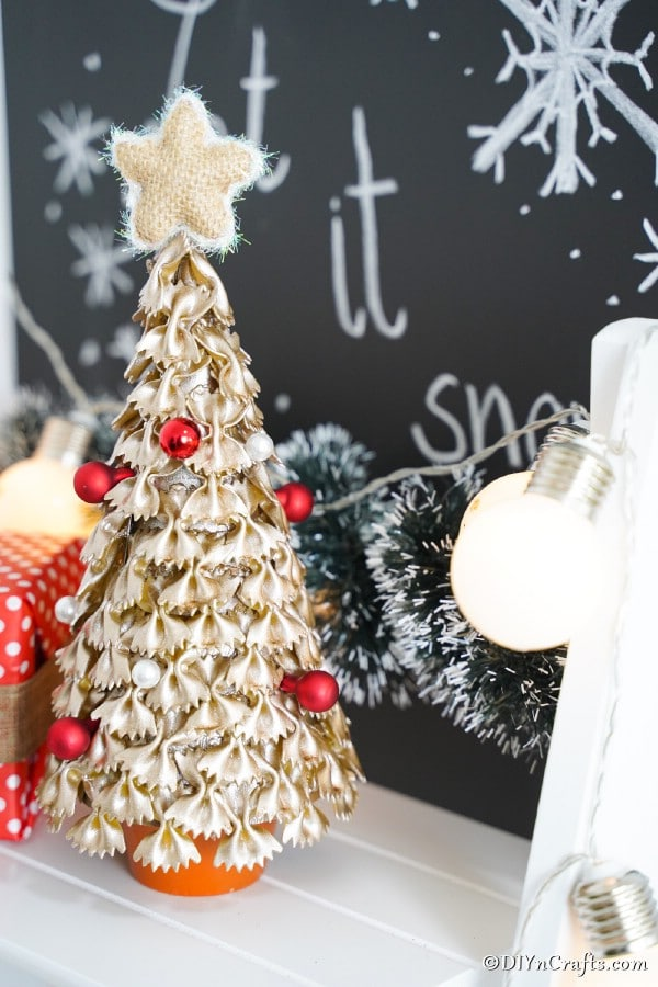 A pasta Christmas tree on a white counter with a Christmas chalkboard in the background