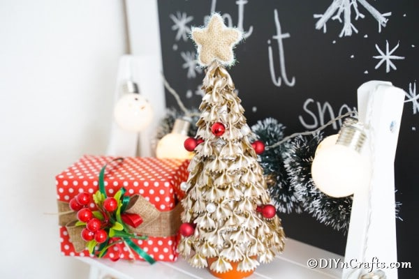 A gold painted Christmas tree decoration made from pasta on a mantle with other holiday decor