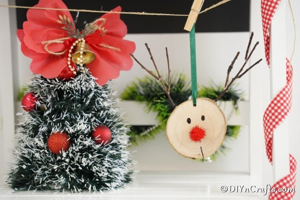 A mini Christmas tree next to a simple wood slice reindeer ornament on a mantle or shelf