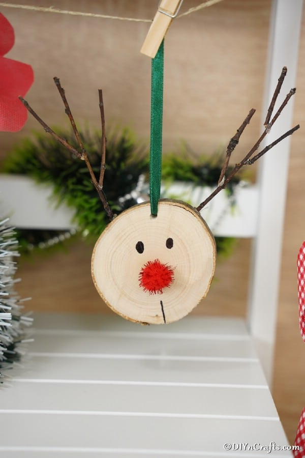 A wood slice reindeer ornament hanging on a branch