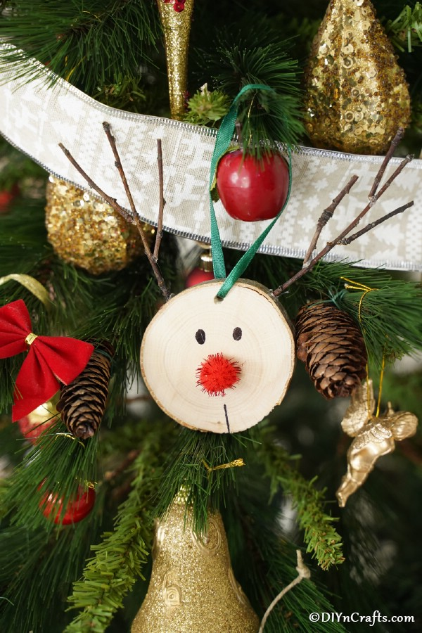 Close up picture of a wood slice reindeer ornament on a Christmas tree