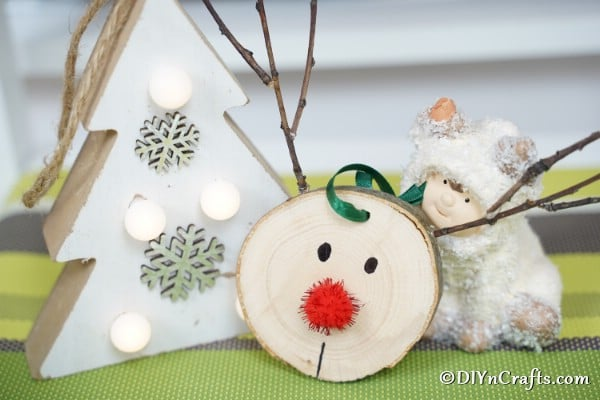 Wood slice reindeer ornament displayed on a green table beside a white holiday tree