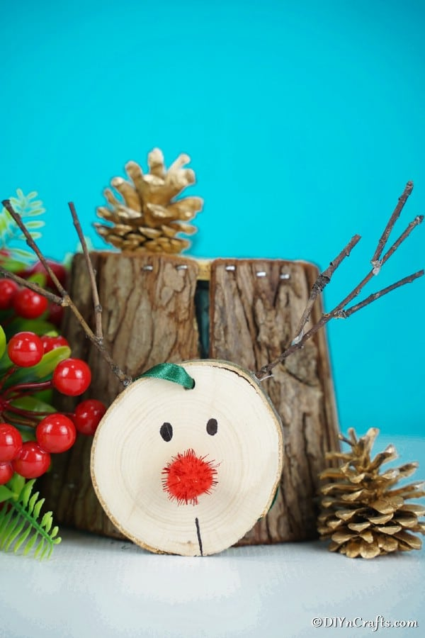 A wood slice reindeer ornament sitting up against a piece of tree trunk with holiday decorations around it