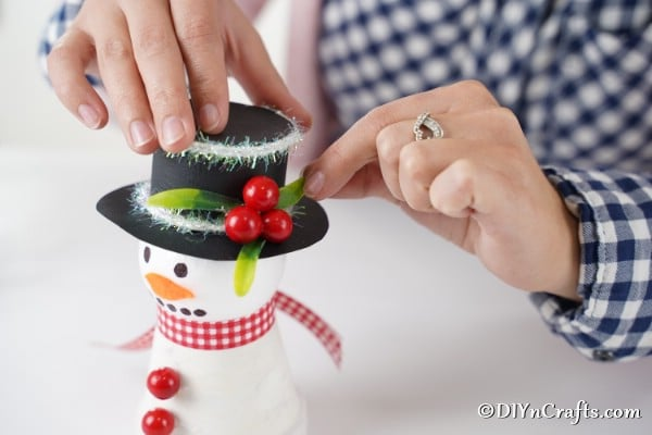 Attaching leaves and berries to top of snowman decoration